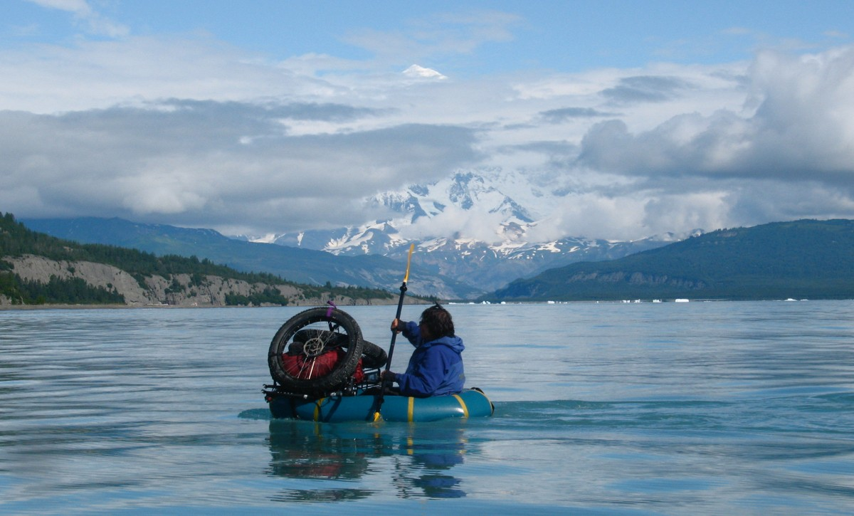 Dylan Kentch paddling across Icy Bay with Mt. Saint Elias in the background. Photo by Eric Parsons, Revelate Designs.